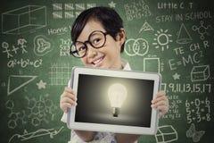 Lo studente attraente mostra la lampadina sulla compressa Fotografia Stock