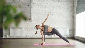 Lo studente avanzato di yoga sta facendo la combinazione di equilibratura e i asanas di potere nel benessere moderno concentrano  stock footage