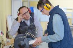 Lo studente In Carpentry Class che usando la circolare ha visto immagine stock