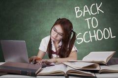 Lo studente castana usa il computer portatile ed i manuali Fotografie Stock Libere da Diritti