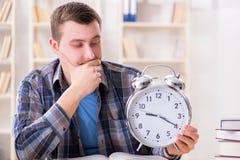 Lo studente che ottiene tardi con la preparazione dell'esame Immagine Stock