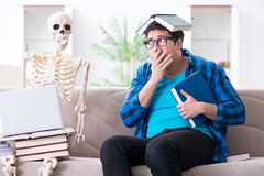 Lo studente che studia con lo scheletro che prepara per gli esami Fotografia Stock
