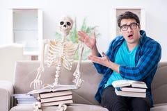 Lo studente che studia con lo scheletro che prepara per gli esami Fotografie Stock Libere da Diritti