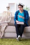 Lo studente che studia con lo scheletro che prepara per gli esami Immagini Stock Libere da Diritti