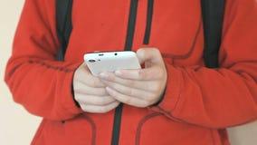 Lo studente che tiene uno smartphone bianco all'interno stock footage
