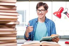 Lo studente con i lotti dei libri che preparano per gli esami Fotografia Stock