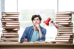Lo studente con i lotti dei libri che preparano per gli esami Immagini Stock