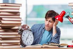 Lo studente con i lotti dei libri che preparano per gli esami Immagine Stock