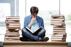 Lo studente con i lotti dei libri che preparano per gli esami Fotografie Stock