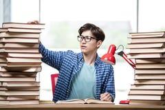 Lo studente con i lotti dei libri che preparano per gli esami Immagine Stock Libera da Diritti