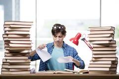 Lo studente con i lotti dei libri che preparano per gli esami Immagini Stock Libere da Diritti