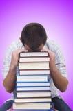 Lo studente con i lotti dei libri su bianco Fotografia Stock Libera da Diritti