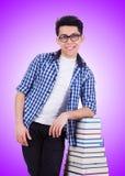 Lo studente con i lotti dei libri su bianco Immagini Stock