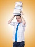 Lo studente con i lotti dei libri su bianco Fotografia Stock