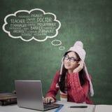 Lo studente con i vestiti dell'inverno pensa i suoi lavori da sogno Fotografia Stock Libera da Diritti