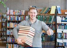 Lo studente con il mucchio prenota la mostra dei pollici su nella biblioteca di istituto universitario Fotografie Stock Libere da Diritti