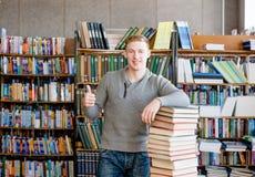 Lo studente con il mucchio prenota la mostra dei pollici su nella biblioteca di istituto universitario Fotografia Stock Libera da Diritti