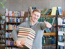 Lo studente con il mucchio prenota la mostra dei pollici su nella biblioteca di istituto universitario Immagine Stock