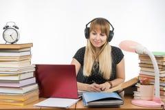 Lo studente con le cuffie pronte a passare il progetto del diploma sta cercando le informazioni su Internet Fotografie Stock Libere da Diritti