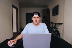 Lo studente con un'espressione sgomento esamina la macchina fotografica mentre si siede nella sua stanza vicino al computer porta Fotografie Stock Libere da Diritti