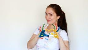 Lo studente del pittore della ragazza sorride e mostra il cuore Amore di arte e della professione Vestiti sporchi e mani sporche  stock footage