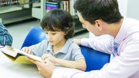 lo studente del ragazzo e dell'insegnante impara con il libro con il backgroun dello scaffale per libri Immagine Stock Libera da Diritti