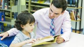 lo studente del ragazzo e dell'insegnante impara con il libro con il backgroun dello scaffale per libri Fotografia Stock Libera da Diritti