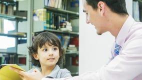 lo studente del ragazzo e dell'insegnante impara con il libro con il backgroun dello scaffale per libri Fotografia Stock