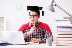 Lo studente dell'eroe eccellente che indossa un tocco che studia per gli esami Fotografia Stock