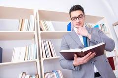 Lo studente dell'uomo d'affari che legge un libro che studia nella biblioteca Fotografia Stock Libera da Diritti