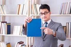 Lo studente dell'uomo d'affari che legge un libro che studia nella biblioteca Immagine Stock