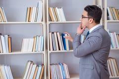 Lo studente dell'uomo d'affari che legge un libro che studia nella biblioteca Fotografia Stock