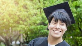 Lo studente dell'uomo sorride e tatto felice in abiti e cappuccio di graduazione Fotografie Stock