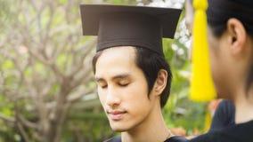 Lo studente dell'uomo sorride e tatto felice in abiti e cappuccio di graduazione Fotografia Stock Libera da Diritti
