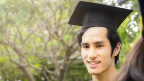 Lo studente dell'uomo sorride e tatto felice in abiti e cappuccio di graduazione Fotografia Stock