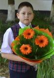 Lo studente della scuola con un mazzo dei fiori luminosi si avvicina alla scuola Fotografia Stock