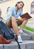 Lo studente della stoppia ha letto un libro che si siede sulle scale in università Fotografie Stock