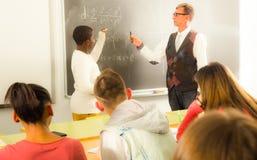 Lo studente di Aframerican risponde vicino alla lavagna alla lezione di per la matematica Immagini Stock