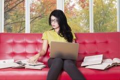 Lo studente di college con il computer portatile legge i libri sul sofà Immagini Stock