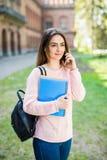 Lo studente di college della ragazza con i libri e la borsa che si siede fuori dell'università e parlano il telefono Immagine Stock