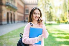 Lo studente di college della ragazza con i libri e la borsa che si siede fuori dell'università e parlano il telefono Fotografia Stock Libera da Diritti