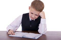 Lo studente di dieci anni della High School che si siede ad uno scrittorio Immagini Stock