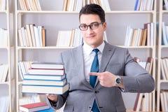 Lo studente di diritto di affari con il mucchio dei libri che lavorano nella biblioteca Fotografia Stock Libera da Diritti