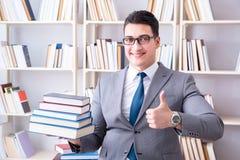 Lo studente di diritto di affari con il mucchio dei libri che lavorano nella biblioteca Immagini Stock