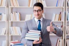 Lo studente di diritto di affari con il mucchio dei libri che lavorano nella biblioteca Immagini Stock Libere da Diritti