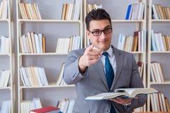 Lo studente di diritto di affari con la lente d'ingrandimento che legge un libro Fotografia Stock