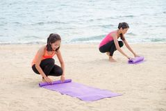 Lo studente di yoga tiene la stuoia di yoga dopo la classe all'aperto della spiaggia di rivestimento, guarisce Fotografia Stock