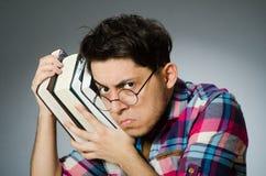 Lo studente divertente con molti libri Immagine Stock
