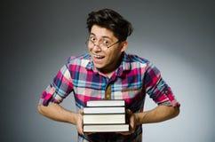 Lo studente divertente con molti libri Fotografie Stock