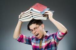 Lo studente divertente con molti libri Immagini Stock